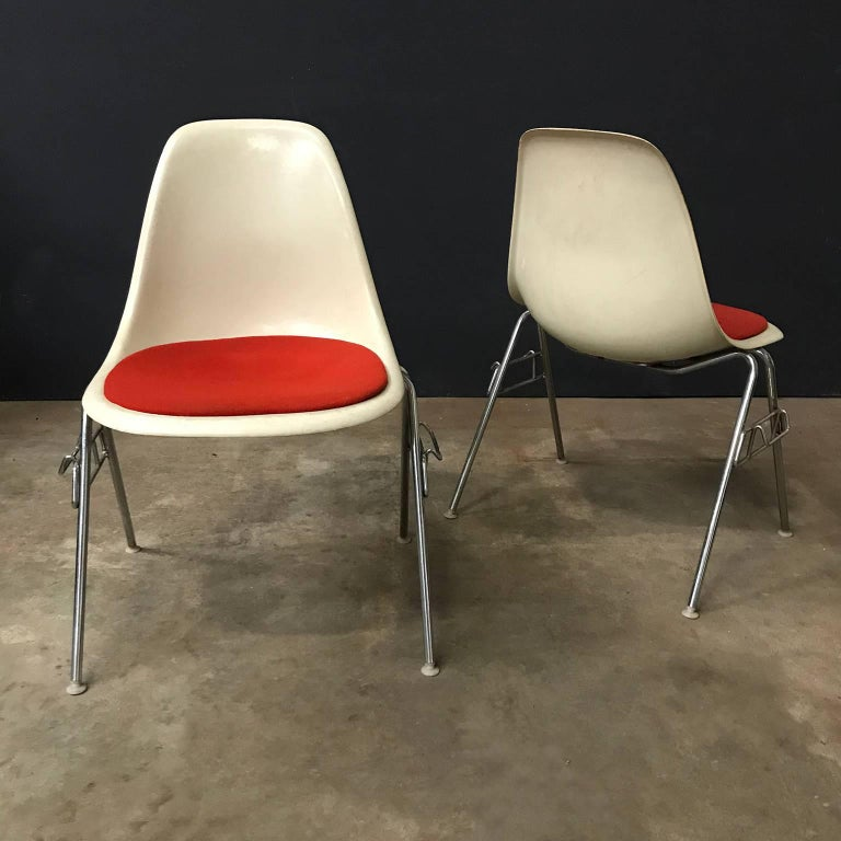 Divers sets of four Eames sideshells with orange pillow by Herman Miller., per piece for sale. Beautiful set. Chairs show traces of wear on the shells and also the pillows show some spots (see picture #5 and #6). Frames have some tiny rusty