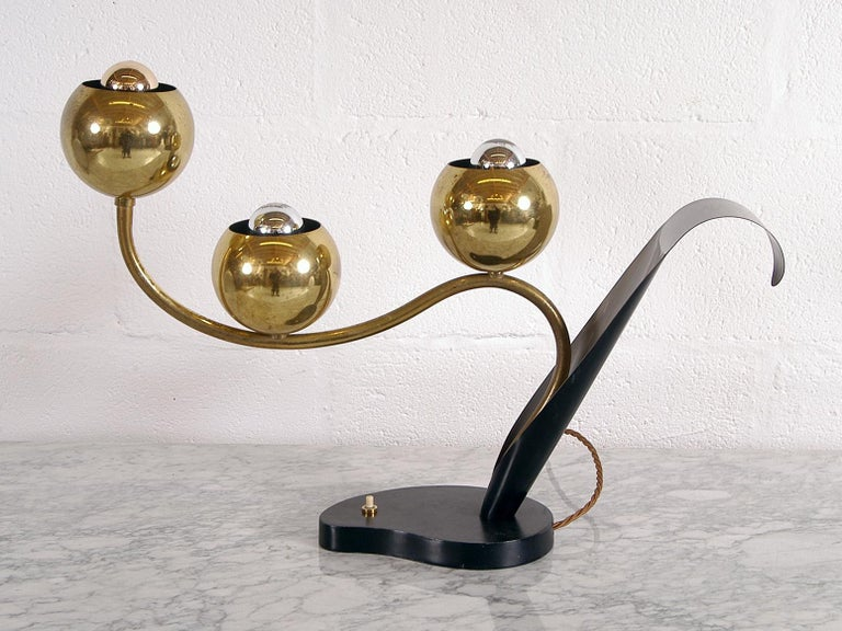Pure 1950s stylish American Kitsch by The Laurel Lamp Company, USA, who were an active tastemaker in Mid-Century Modern lighting from the 1950s-1970s. This incredibly elegant lamp is in the form of a stylized flower, where three brass ball shades