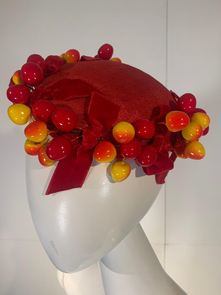 A delicious 1950s scarlet red straw topper hat adorned with blushing Merten cherries and red velvet bows. Styled by Frances. Side tabs for pinning. So charming! One size.