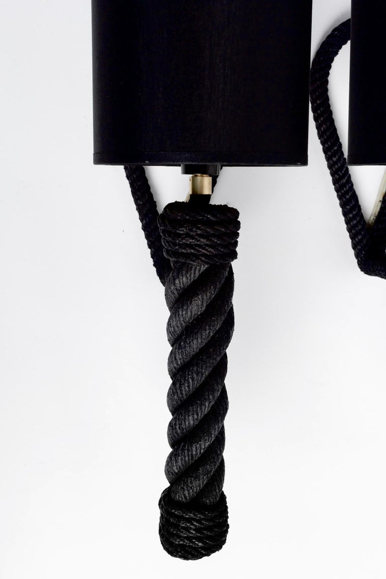 Composed of a rope arm of round section adorned with a wall attachment forming a loop and dressed with a cylindrical black cotton lampshade enhanced at the base of the torch with a gilded brass ring. 1 bulb  The string of the appliques has been