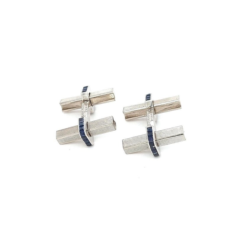 Cufflink design composed of two gold bars with ridged detailing linked by a sapphire set stirrup shaped panel with polished edges, with a twist and pull movement, circa 1950.  Sapphire: 44 Sapphires Princess cut, ca.3,08 ct  Material: 18kt white