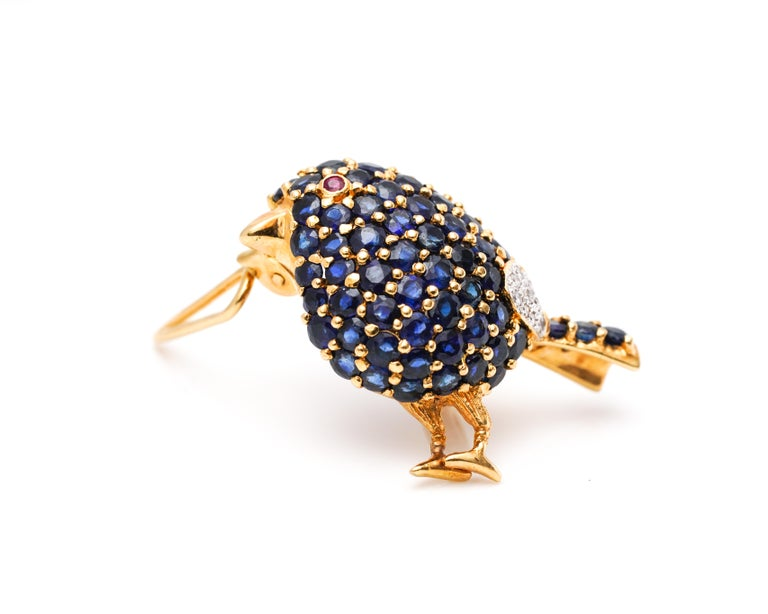 Bird Details: Metal type: 18 Karat Yellow Gold Weight: 7.5 grams  Features 1 Carat of Sapphires, Natural Blue in Color (body) Features Accent Ruby (eye) and Diamonds (near the tail)  Dates back to 1950s