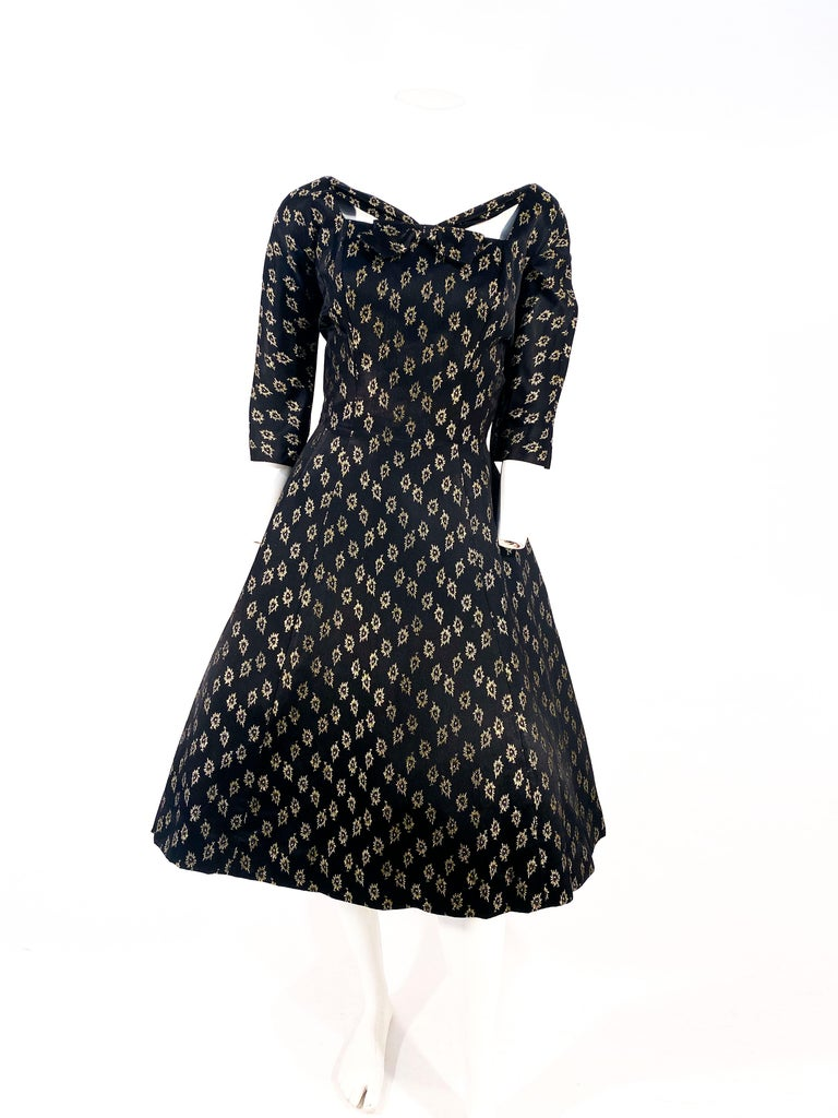 Late 1950s to early 1960s Suzy Perette cocktail dress featuring a black satin brocade detailed with gold metallic lurex in a repeating floral motif. The bodice is structured and fitted with three-quarter length sleeve, and a modified striped square