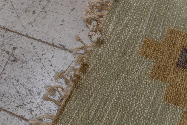 A 1950/60s Swedish flat weave rug initialled with the insignia IR Ida Rydelius. IDA was a well-known textile artist recognised for her unusual and fabulous designs.  The rug features a lovely, muted, sage-green, background. Overlaid is a design of
