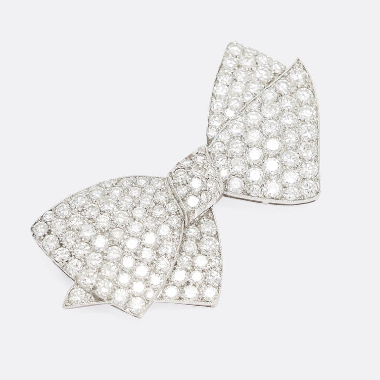 A stunning 1950s bow brooch crafted in platinum and pavé set with over 4.75 carats of brilliant cut diamonds (G-VS). It's exceptionally well worked, wonderfully proportioned and full of life, it's finished with fine millegrain edges and open