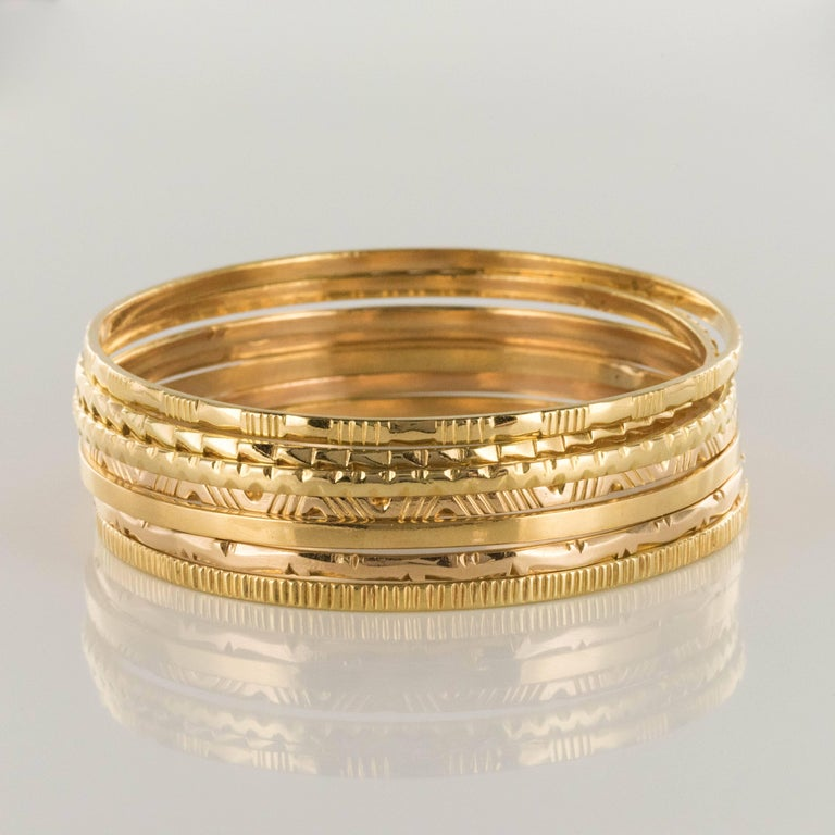 Bracelet in 18 karats yellow gold. This bracelet is made up of 7 round half bangles in yellow gold and engraved each with a different decoration. The bangles can be worn together or separately and slip on. Inner circumference: 19 cm, width: 2.6 mm,