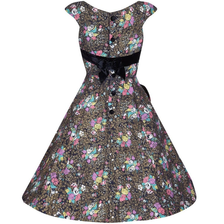 This charming 1950s cotton dress has a print of rose bunches in an assortment of pastel shades - pink, lilac, yellow,  jade green and white, which lie in between beds of gold printed daisies on a black background. The dress has a boat neckline with