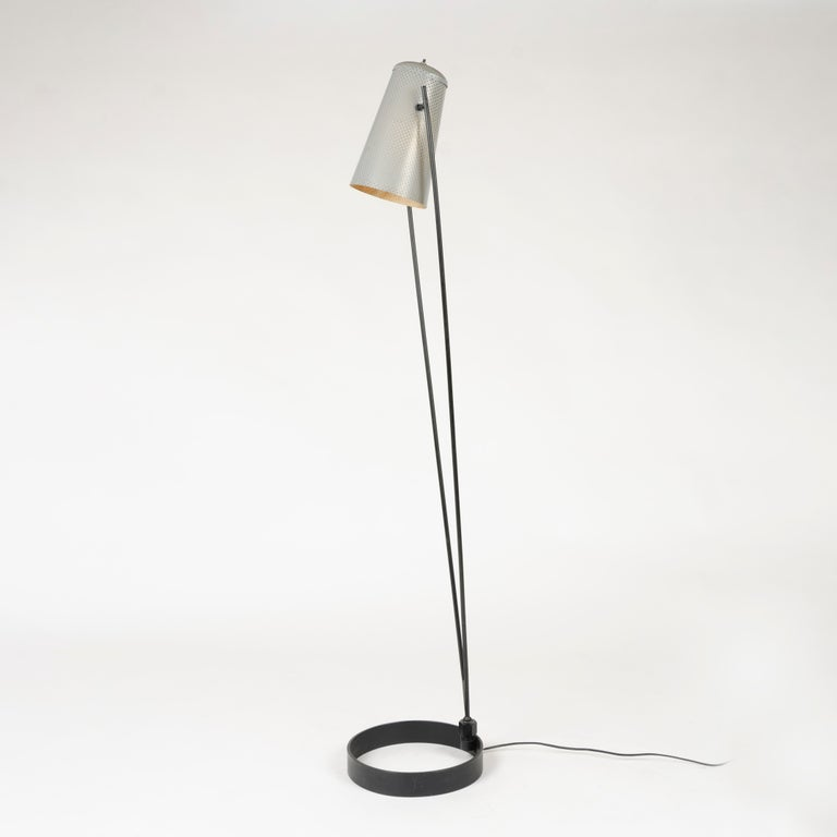 A unique adjustable perforated-aluminum shade in original grey finish floating between two metal rods that swivel at enameled-iron circular base. Model 5006.