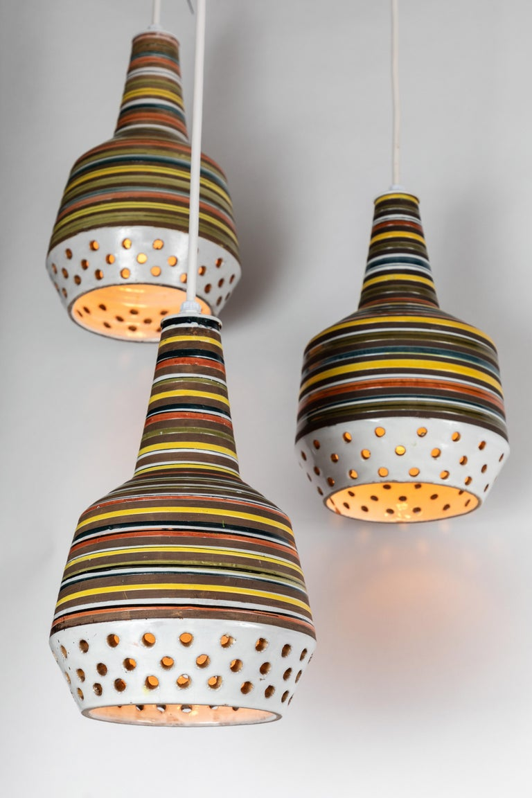 1950s Aldo Londi ceramic Bitossi pendant lamp for Italian Raymor. This rare and sculptural Italian ceramic lamp is executed with multicolored glazed horizontal stripes and geometric circular perforations.  Please note, two lamps available.  Ceramic