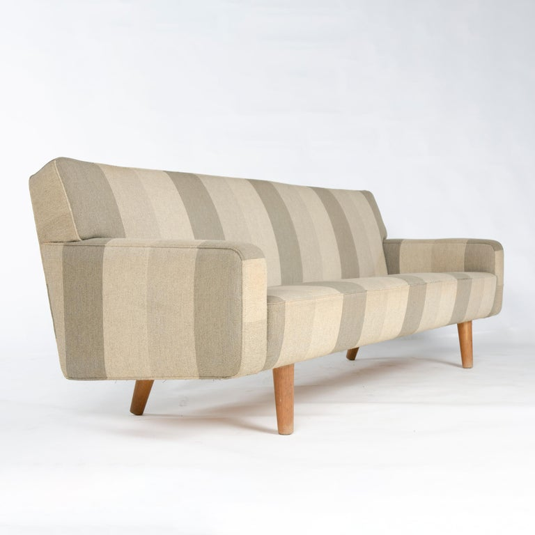 A tailored and fully upholstered sofa floating on well-scaled turned oak dowel legs. Model AP32-S by Hans J. Wegner for A.P. Stolen in original upholstery.