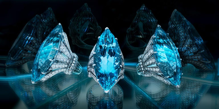 Claw-set with a marquise shape mixed-cut aquamarine weighing approximately 25 cts, to an high carved gallery set with brilliant cut diamonds.  The diamonds weighing approximately 2 cts    Mounted in 18Kt white gold    Finger size: 7    Weight: