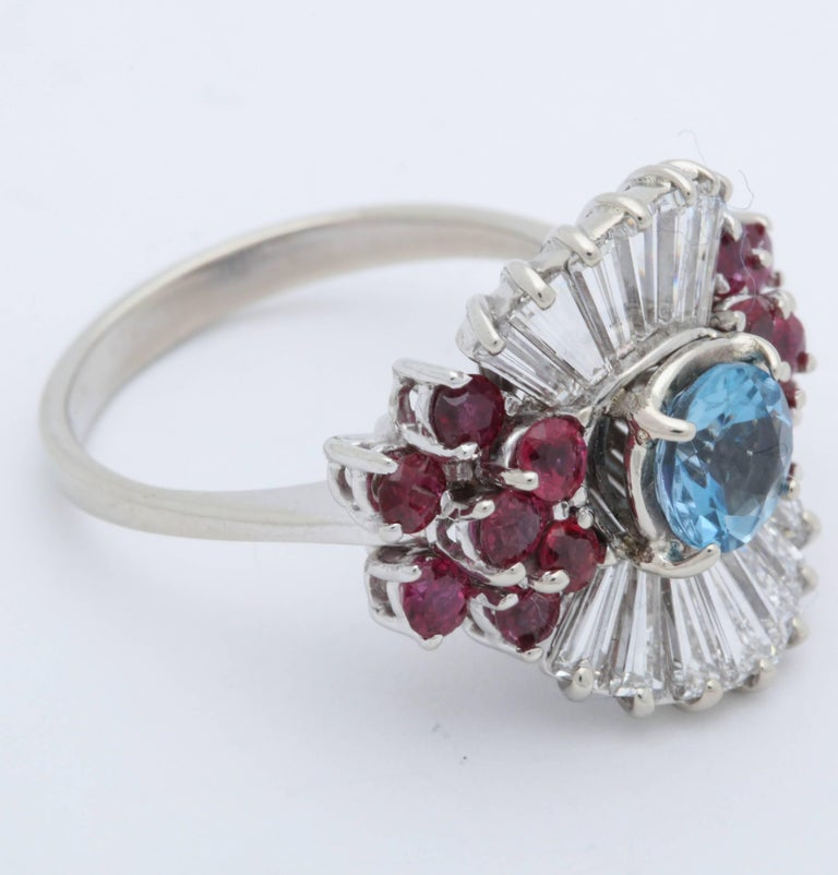 One Ladies 14kt White Gold Ballerina Ring Designed with a One Carat Beautiful Color Prong Set Aquamarine Stone,Ring Is Also Embellished With Numerous Fan Shaped Tapered Baguette Diamonds Weighing Approximately 1.50 Carats Total weight. This Fancy