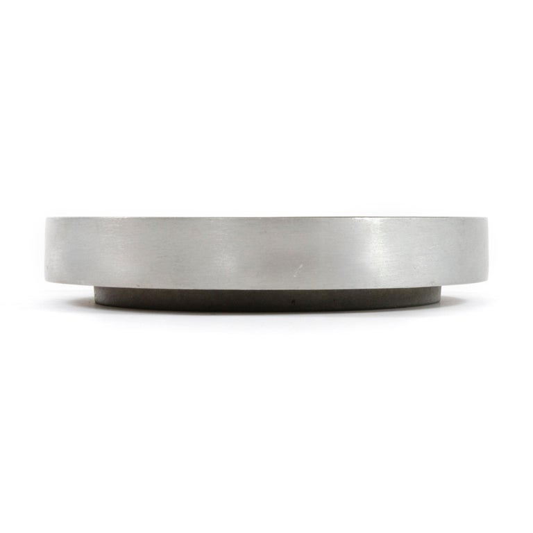 A large scale cast aluminum ashtray with concentric circles.