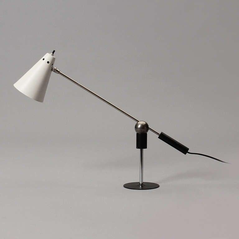 An articulating desk lamp with a cone shaped shade on a metal base and a magnetic ball connection to allow movement.
