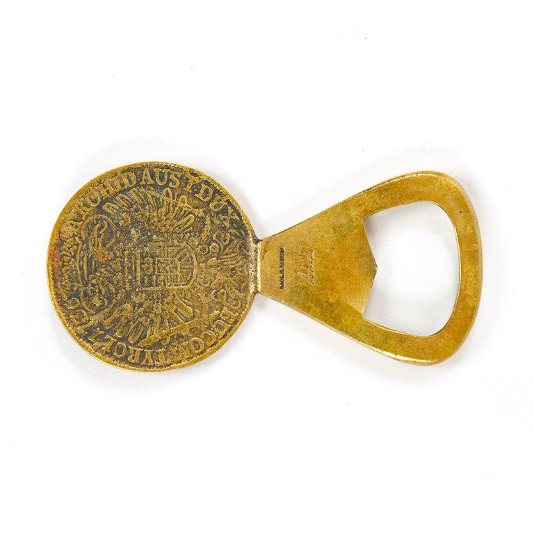 A coin-shaped brass bottle opener.