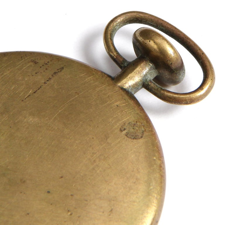 A patinated bronze paperweight in the form of pocket watch.