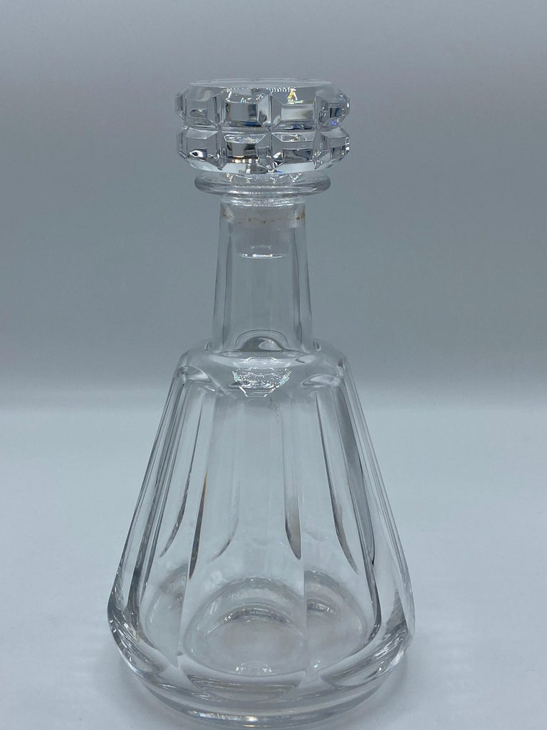 Product details:  The decanter is designed by Baccarat in France and it is made out of crystal, featuring geometric cut motif. The measurements are 9.5 inches high and 5 inches wide. The weight is 1306.0 grams.