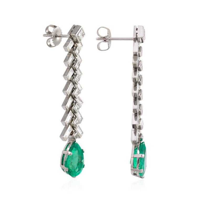 A pair of diamond pendant earrings designed as a line of chevroned baguettes terminating in a faceted pear-shaped emerald drop, in platinum. Emeralds approx. 1.58ct., 1.95ct.; atw. 3.00 ct. square step cut and baguette cut diamonds.