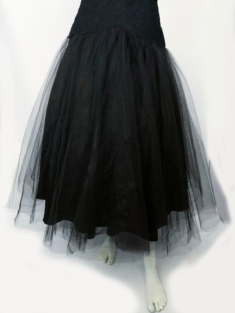 Black cocktail dress with a lace overlay on the bodes the is structured with layered racing and serves as a modesty panel. The drop-waist is accentuated by  a tule overskirt. The entire skirt is lined with a black taffeta.