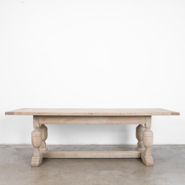A bleached oak dining table from Belgium, circa 1950. A square tabletop, turned legs and a sturdy central strut create a farmhouse Silhouette. The heft and solidity of this table don't impede its decorative charm, accentuated by the light finish of