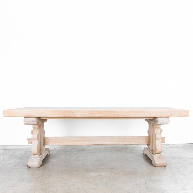 A bleached oak dining table made in Belgium, circa 1950, featuring trestle legs with a curved, heraldic profile. The legs are joined by a strut held in place with pegs and slats, yielding a design that is both stately and provincial. The sturdy