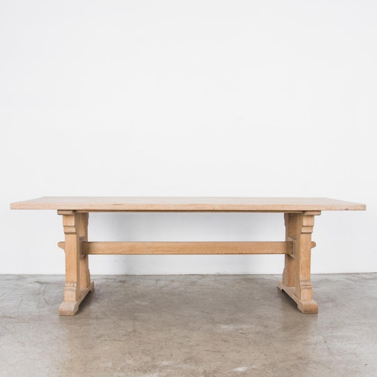 """An oak trestle table from Belgium, circa 1950. A striking H-shaped leg construction atop a pair of rounded braces supports a long tabletop, measures: 95"""". The legs are joined by a trestle and held in place with wooden pins, a design that is both"""