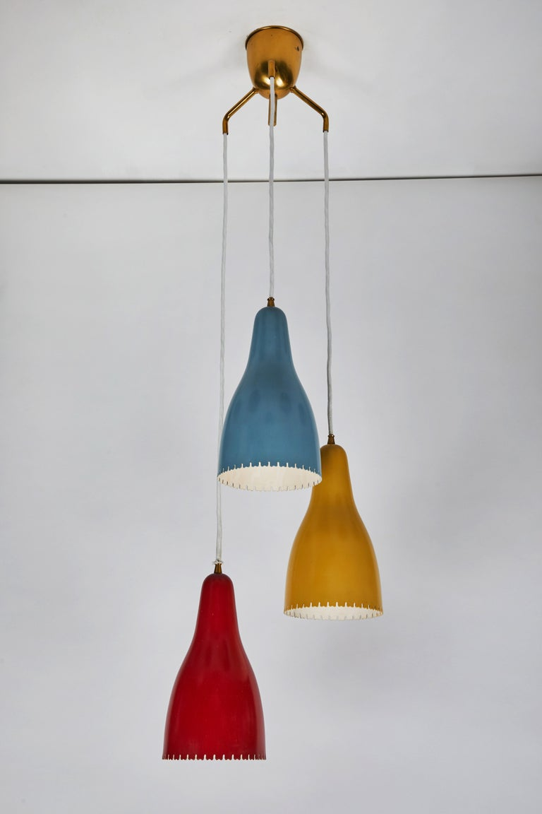 1950s Bent Karlby pendants for Lyfa. Executed in architecturally cut and elegantly shaped multi-color painted metal shades with brass hardware, Denmark, circa 1950s. A quintessentially Danish Modern chandelier by a master Swedish designer whose