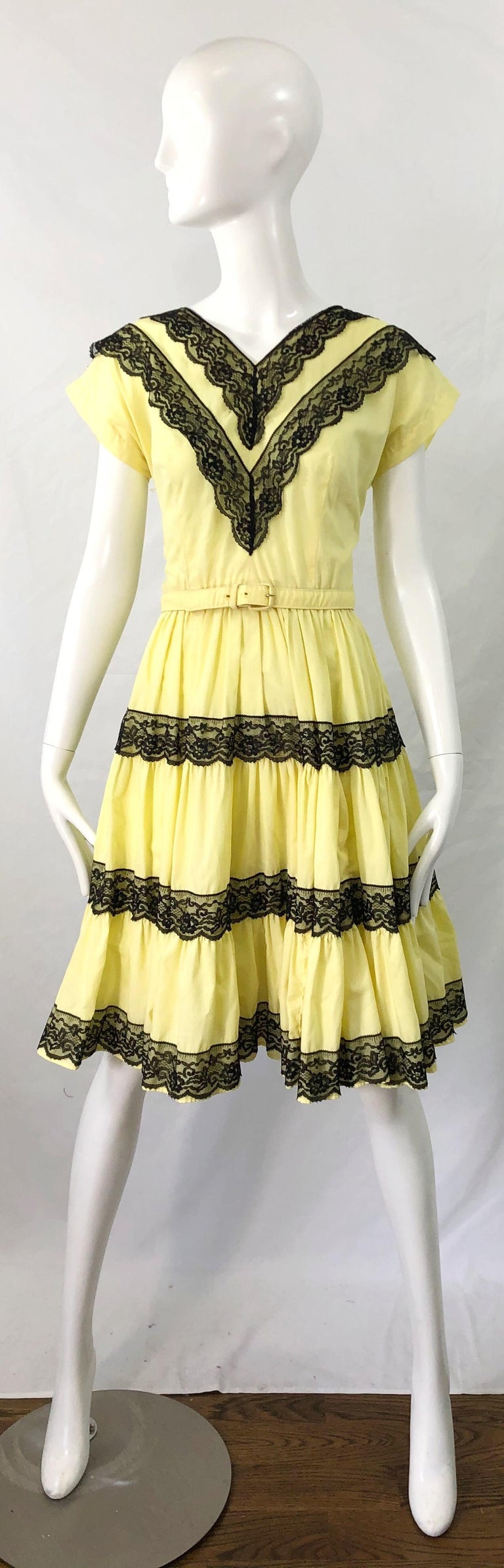 Beautiful 1950s BETTINA OF MIAMI lightweight cotton and lace fit n' flare belted dress ! Features a pale yellow cotton and black lace. Fitted tailored bodice with a forgiving full skirt. Full metal zipper up the back with  hook-and-eye closure.