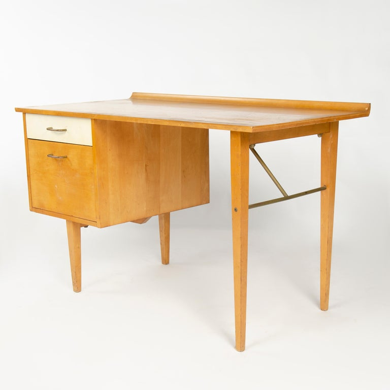 A birch desk with gallery edge, file drawer and pencil drawer with white laminate front over tapered legs with steel hardware.