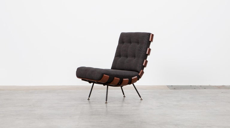 Wonderful Brazilian lounge chair designed by Martin Eisler and Carlo Hauner. The chair has been produced in rosewood and plywood slats bent elegant to the ends and stands on a black lacquered metal frame with brass feet. The cushions are recently