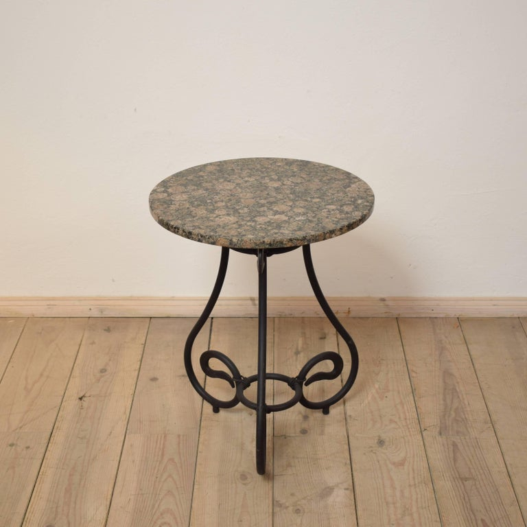 This forged iron side table was made in the 1950s by a German Blacksmith in South Germany. It is very nice made and it has got a granite top. The granite top has a lot of different colors. A beautiful and elegant piece which fits to the most
