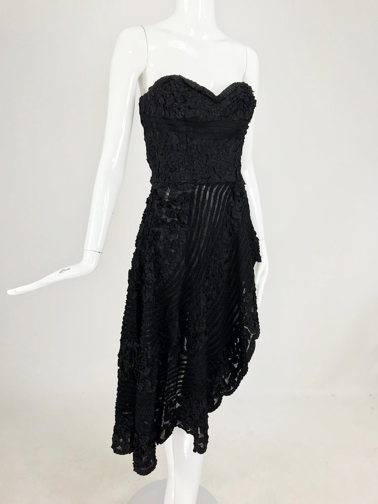 1950s Black Ribbon Work Strapless Asymmetrical Dress. This amazing piece is professionally handmade from the 1950s, the fabric is sheer black with narrow ribbons of black taffeta that are machine stitched in geometric patterns. The strapless, sweet