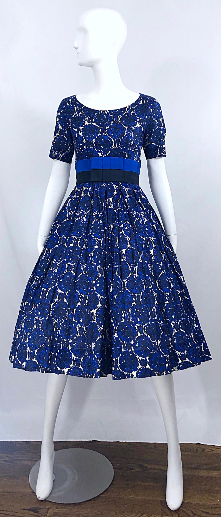 Phenomenal vintage 50s BONWIT TELLER demi couture blue abstract flower print fit n' flare cotton dress! Features a fitted bodice, with two bands of silk grosgrain bows in blue and black. Full skirt has plenty of room to accomodate a crinoline for