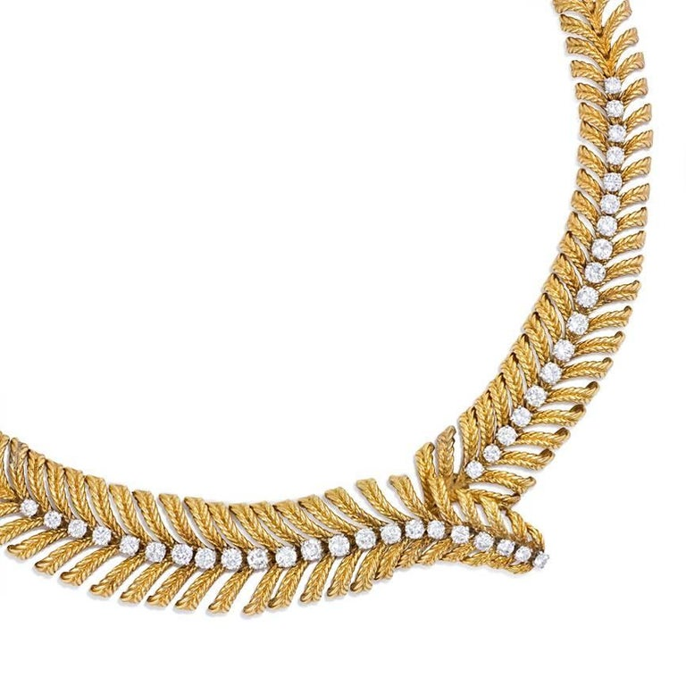 A gold and diamond necklace of stylized plume design with a tapered bypass central motif, in 18k and platinum.  Atw. 6.00 ct. diamonds. Boucheron, Paris