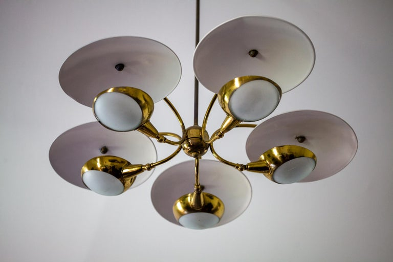 Brass and painted aluminum shades. This whimsical 5-light chandelier is stem mounted. User may cut the stem if a shorter length is desired. Omits a beautiful warm-toned reflective glow from the off-white shades and frosted glass.