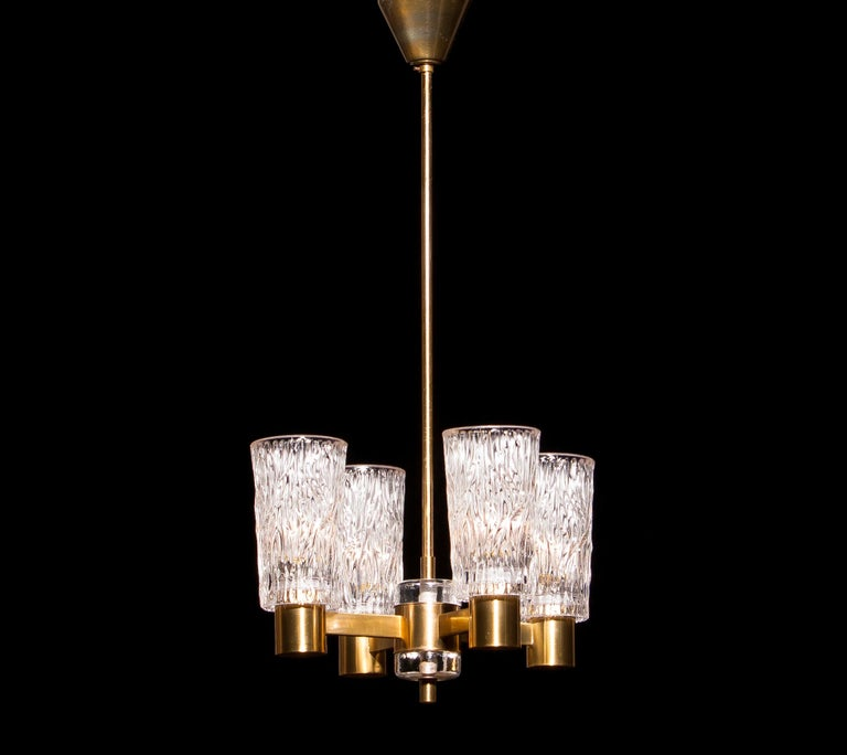 Beautiful chandelier made by Orrefors, Sweden. This lamp is made of brass with four clear crystal glass shades. It is in a lovely condition. Period: 1950s. Dimensions: H 65 cm, ø 35 cm.