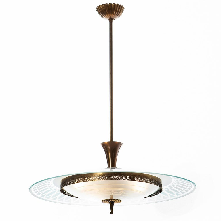 This stunning and super elegant light consisting of a brass frame and 2 unique glass reflector/saucers.  The lower round curved glass reflector with gold patterns mounts below a larger round etched & clear glass reflector. A beautiful, decorated
