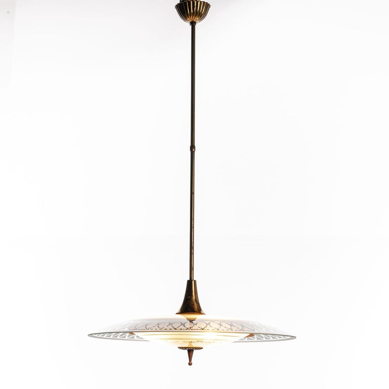 This super elegant light consisting of a brass frame and 2 unique glass reflector/saucers.  The lower round curved glass reflector with gold patterns mounts below a larger round etched & clear glass reflector. A beautiful, decorated brass ring to