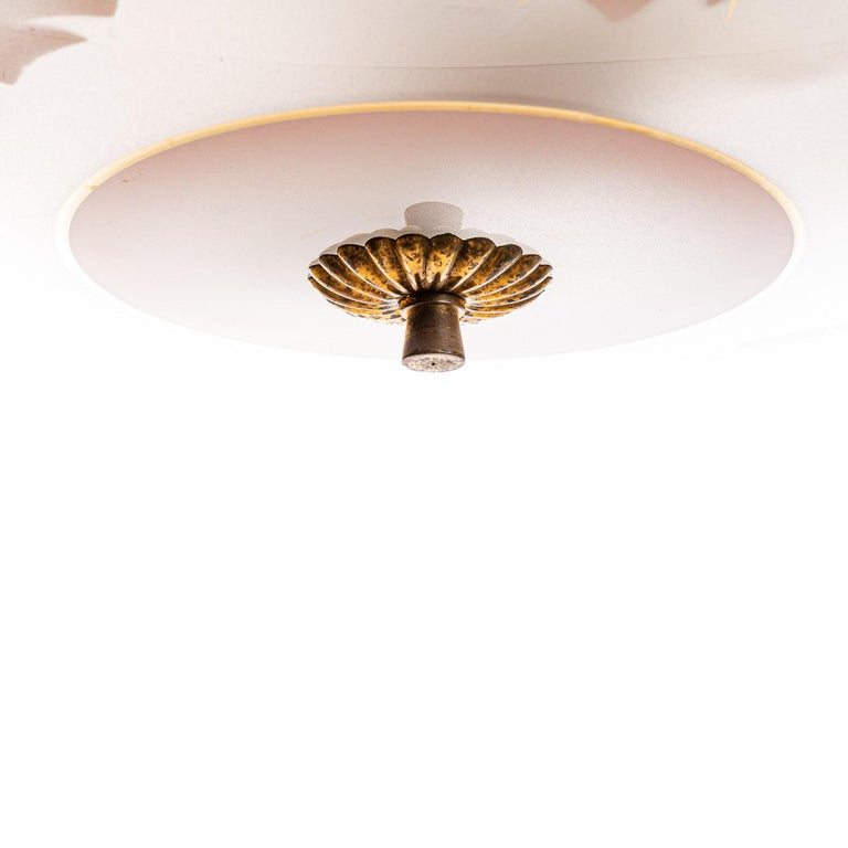 This elegant piece consisting of a brass frame and 2 unique frosted and satin glass reflector/saucers.  The lower round curved glass reflector with a colorful pink floral motif mounts below a round satin glass reflector. Finished off with a brass