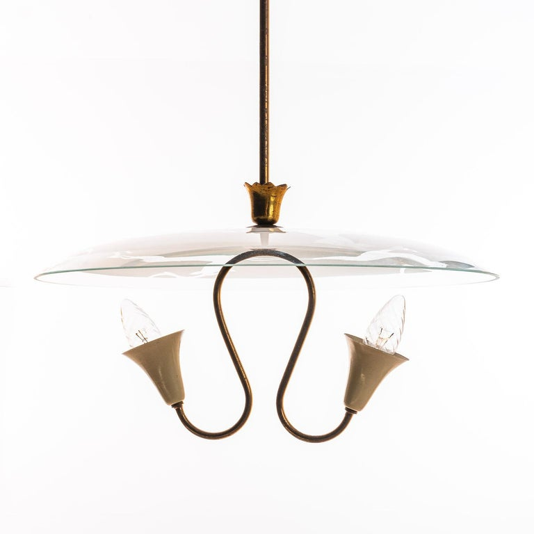 This elegant piece consisting of a brass frame and a unique frosted and satin glass reflector/saucers with dear engraving. Brass hardware and stem with two E14 electrical sockets.