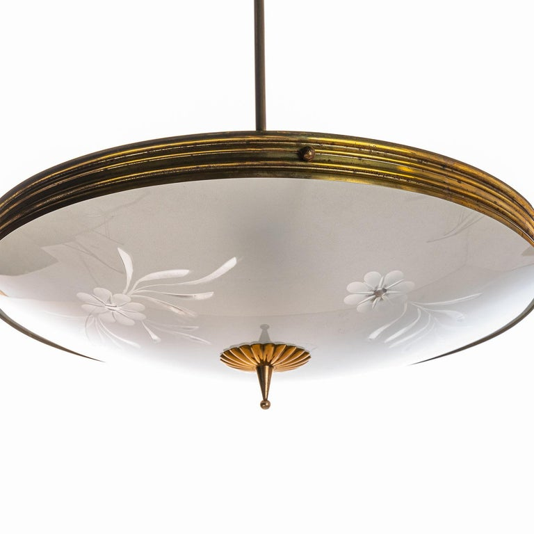 his elegant piece consisting of a brass frame and 2 unique frosted and satin glass reflector/saucers.  The lower round curved glass reflector with floral engraving mounts below a round satin glass reflector. Finished off with alarger brass