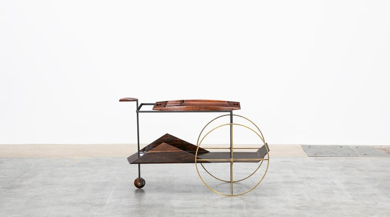 This Brazilian modern classic piece was designed in 1959 by Jorge Zalszupin. The exquisite barcart is made in Brazilian jacaranda with brass wheels. The top shelf is a removable tray. Noble lines, the essential use of native wood and a combination