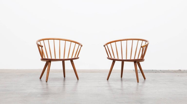 Two beautiful lounge chairs designed by Yngve Ekström. Simple and stylish Swedish furniture design, in highly attractive, warm oakwood. Elegantly curved backrest and a elliptical seat on tapering legs. Manufactured by AB Stolfabriks.  Yngve