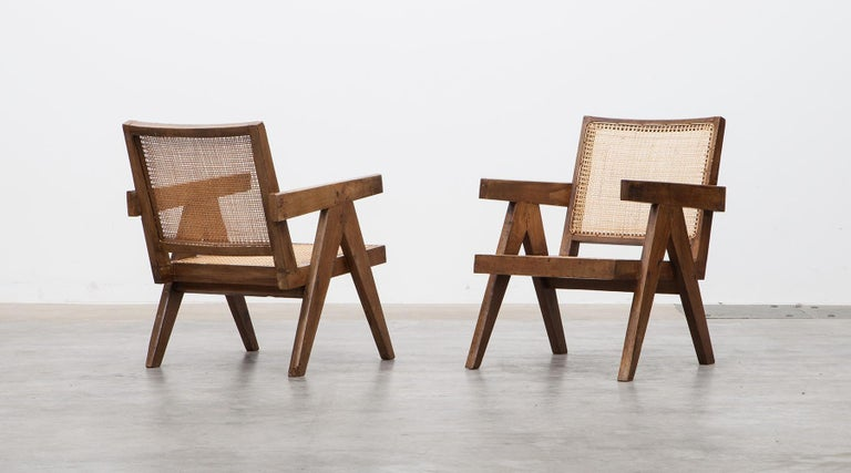 Pair of lounge chairs designed by Pierre Jeanneret in teak, Chandigarh, India, 1955  These original lounge chairs designed by Pierre Jeanneret in teak with woven cane on the seat and curved backrest appears in beautiful patina. Considering India
