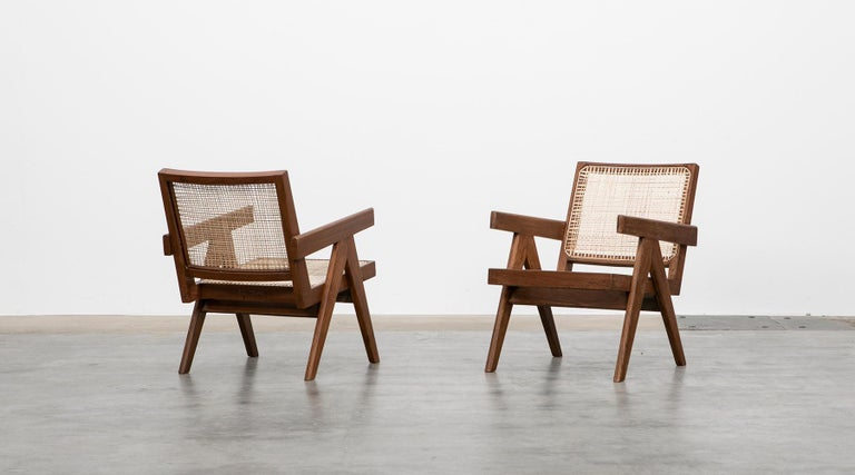 Pair of lounge chairs designed by Pierre Jeanneret in teak, Chandigarh, India, 1955.  These original lounge chairs designed by Pierre Jeanneret in teak with woven cane on the seat and curved backrest appears in beautiful patina. Considering India