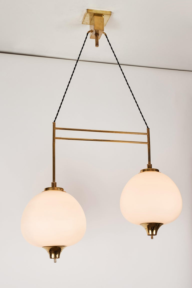 1950s Bruno Chiarini double pendant suspension lamp for Stilnovo. A quintessentially 1950s Italian design executed in two cascading matte finish opaline glass pendants with sculptural brass hardware and the original architectural ceiling canopy