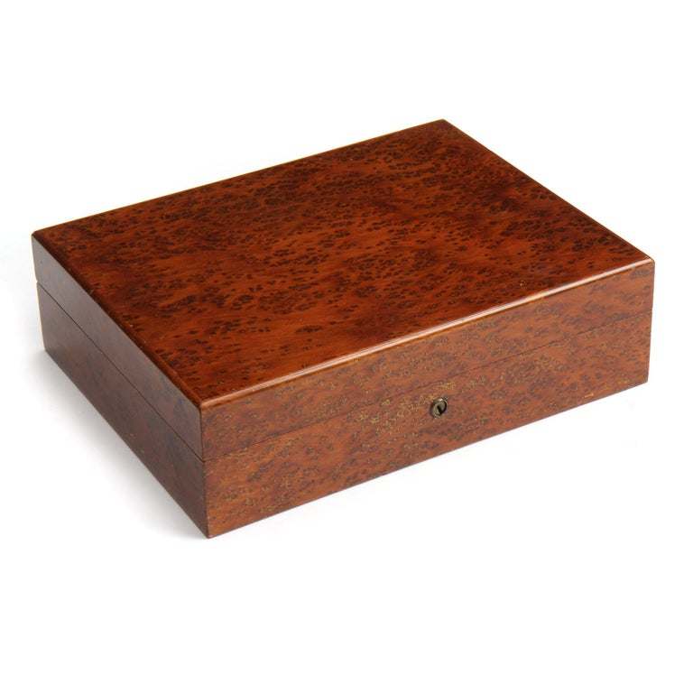 A humidor made of warmly toned burled maple with a cedar and glass interior.