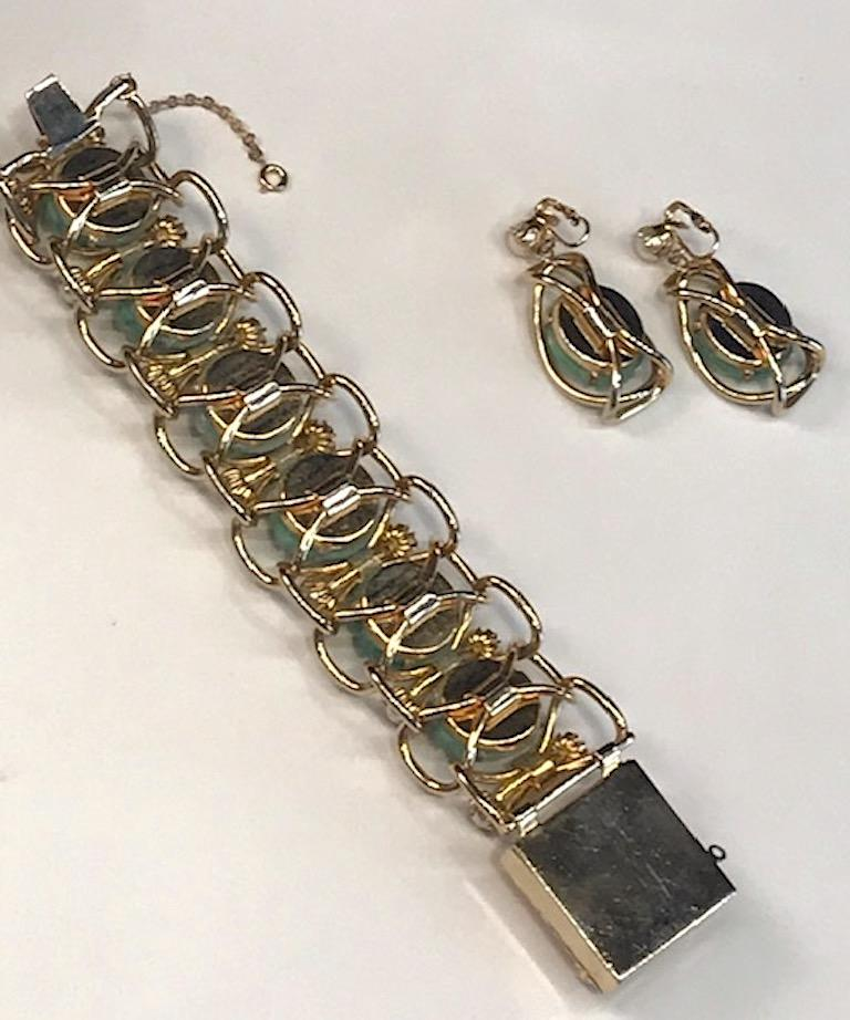 A lovely 1950s bracelet and earring set with carved faux Peking glass and pearls. Each glass piece has streaks of white to simulate authentic Peking glass in a floral motif and is .88 of an inch in diameter. The bracelet measures 1.5 inches wide,
