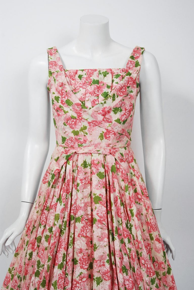 This is such a romantic and elegant 1950's sundress from the iconic Ceil Chapman designer label. Perfect for any spring or summer party; you can't help but feel feminine in this beauty. The garment is fashioned from a pink carnation floral print