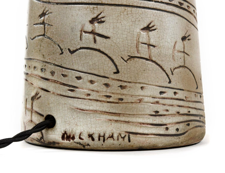 A beige and brown ceramic table lamp with incised decoration, signed 'Wickham,' with a base height of 17